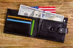 One hundred dollars banknote reach out out of a black old purse. Stock Photos