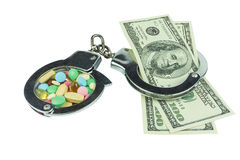 One hundred dollars banknotes and pills in handcuffs Stock Image