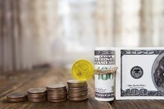 One hundred dollars banknotes of the stack of coins from quarters and one dollar. Copy paste Stock Photos