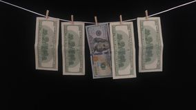 One hundred dollars banknotes weigh on a rope in a row with clothespins. Banknotes of one hundred dollars hang on a rope with clothespins. The concept of dirty stock video footage