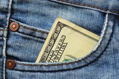 One hundred dollars bill in the pocket of blue jeans close up royalty free stock photos