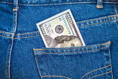 One hundred dollars bill sticking out of the jeans pocket Stock Photo