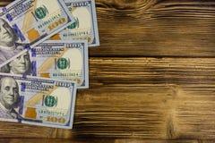 One hundred dollars bills on wooden desk. One hundred dollars bills on the wooden desk Royalty Free Stock Photography