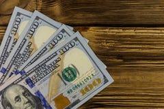 One hundred dollars bills on wooden desk. One hundred dollars bills on the wooden desk Stock Image