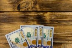One hundred dollars bills on wooden desk. One hundred dollars bills on the wooden desk Royalty Free Stock Images