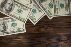 One hundred dollars bills on wooden desk. Top view, copy space Stock Images