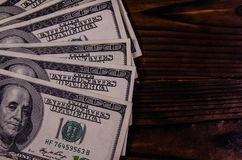 One hundred dollars bills on wooden table. Top view. One hundred dollars bills on rustic wooden table. Top view Royalty Free Stock Images