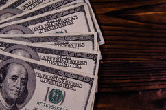One hundred dollars bills on wooden table. Top view. One hundred dollars bills on rustic wooden table. Top view Stock Photo