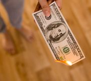 One hundred dollars burn in flames in hand.  Royalty Free Stock Images