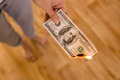 One hundred dollars burn in flames in hand.  Stock Images