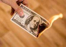 One hundred dollars burn in flames in hand Stock Photos