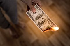 One hundred dollars burn in flames in hand Royalty Free Stock Image