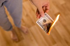 One hundred dollars burn in flames in hand.  Stock Photo