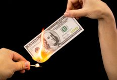 One hundred dollars burn in the hand on a black background.  Stock Photo