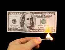 One hundred dollars burn in the hand on a black background.  Royalty Free Stock Photos