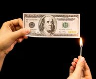 One hundred dollars burn in the hand on a black background.  Stock Image