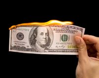 One hundred dollars burn in the hand on a black background.  Royalty Free Stock Image