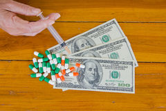One hundred dollars with capsules and hand Royalty Free Stock Photo