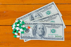 One hundred dollars and capsules on wood background Royalty Free Stock Photos