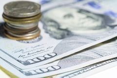 One hundred dollars and coin stack close up with selective focus Royalty Free Stock Image