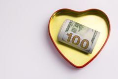 One hundred dollars in a gold heart shaped box with a red outline. Concept for the holiday St. Valentine`s Day, a gift. One hundred dollars in a gold heart Stock Images