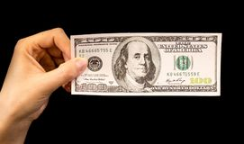 One hundred dollars in a hand on a black background.  Royalty Free Stock Photography