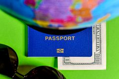 One hundred dollars and a passport on a green background with a map of the globe. 2018 Stock Photo