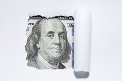 One hundred dollars through torn white paper. Stock Photo