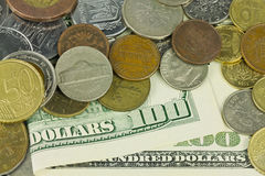 One hundred dollars under coins Stock Photography
