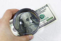 One hundred dollars under the magnifying glass Stock Image