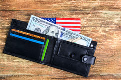 One hundred dollars in the wallet and the American flag. Royalty Free Stock Photos
