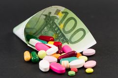 One hundred euro banknote with medical pills. On dark background Royalty Free Stock Image