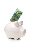 One hundred euro banknote and two euro coin insert into white porcelain pig Royalty Free Stock Images