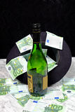 One hundred euro banknotes with a black hat bottle of cognac. On the marble table on a black background Royalty Free Stock Photography