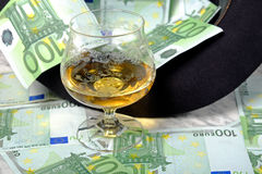 One hundred euro banknotes with a black hat glass of cognac. On a marble table on a black background Stock Images