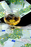 One hundred euro banknotes with a black hat glass of cognac. On a marble table on a black background Stock Photos