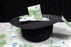 One hundred euro banknotes with a black hat. On a marble table on a black background Royalty Free Stock Photo