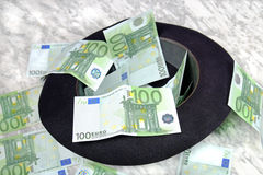 One hundred euro banknotes with a black hat. On a marble table on a black background Stock Photos
