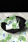 One hundred euro banknotes with a black hat. On a marble table on a black background Royalty Free Stock Photos