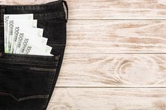 One hundred euro banknotes in a jeans pocket on white wooden background with copy space for your text. Top view.  Stock Images