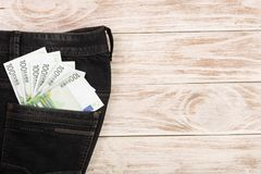 One hundred euro banknotes in a jeans pocket on white wooden background with copy space for your text. Top view.  Stock Image