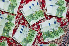 One hundred euro banknotes. Lie on a red carpet, euro banknotes with an oriental carpet background Royalty Free Stock Photos