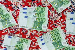 One hundred euro banknotes. Lie on a red carpet, euro banknotes with an oriental carpet background Stock Photos