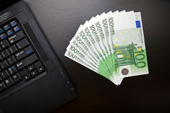 One hundred euro bills and laptop Stock Photo