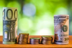 One hundred euro and one hundred US dollar rolled bills banknote. S, with euro coins and american cents on green blurred bokeh background Royalty Free Stock Images