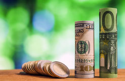 One hundred euro and one hundred US dollar rolled bills banknote. S, with euro coins and american cents on green blurred bokeh background stock photo
