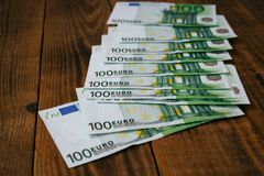 A one hundred euros bills on a wooden background. One hundred euros bills on a wooden background stock photos