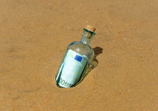 One hundred euros in a bottle on the sand of the beach Stock Photography