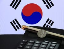 One hundred Korean won coin on obverse, KRW on black calculator with black and white pencil on black floor and Korean flag. One hundred Korean won coin on stock images