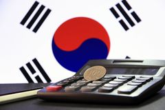 One hundred Korean won coin on reverse, KRW on black calculator with black and white pencil on black floor and Korean flag. One hundred Korean won coin on royalty free stock images